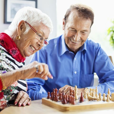 winter date ideas - Happy senior couple playing chess at table in nursing home