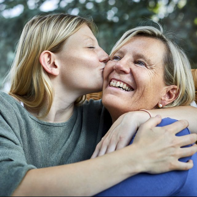 Happy senior woman and young woman hugging and kissing in armchair