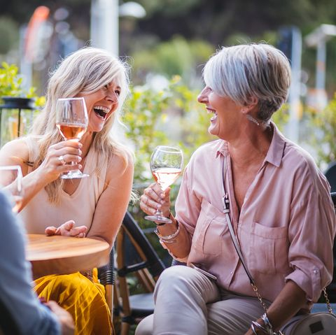 Happy senior women drinking wine and laughing together at restaurant