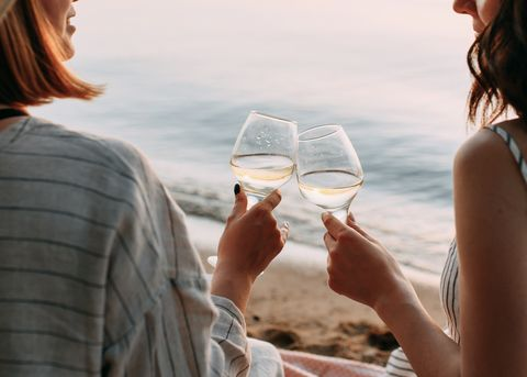 happy smiling people holding glasses drink wine on the beach at sunset