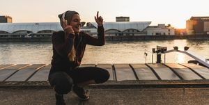 Happy sportive young woman listening to music at the riverside in the city at sunset