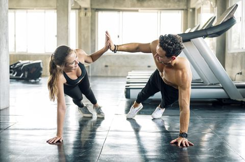 happy sporty couple giving high five to each other while doing push up or side plank exercise together in gym