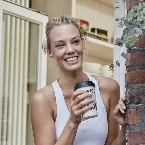 Happy sporty young woman with takeaway drink at house entrance