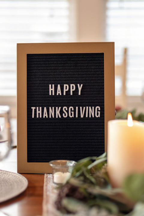 Happy Thanksgiving letterboard on dining room table decorated for dinner party