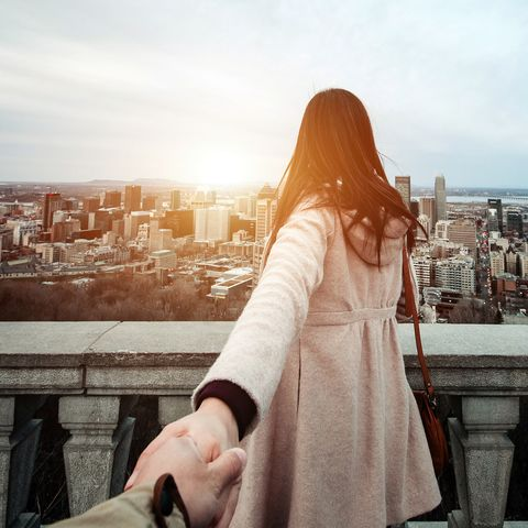 Happy traveller couple holding hands enjoying the spectacular city skyline of Montreal from view point