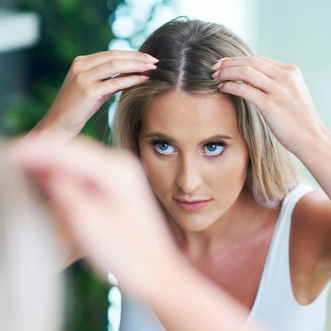 happy woman brushing hair in bathroom having problem with hair loss