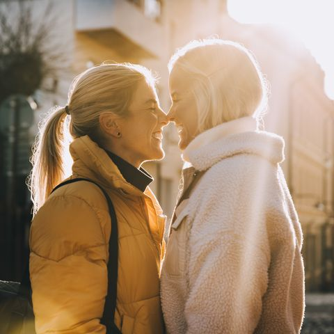 happy woman embracing female partner with closed eyes while standing in city