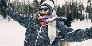 Happy woman enjoying with friend at snowy field