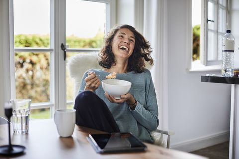 happy woman having breakfast at dining table