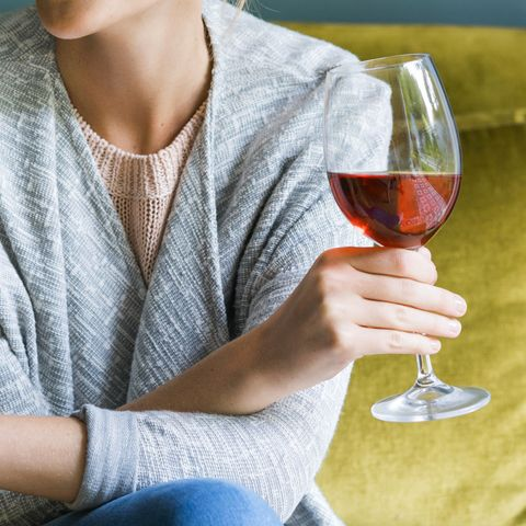 Happy woman holding glass of red wine on sofa