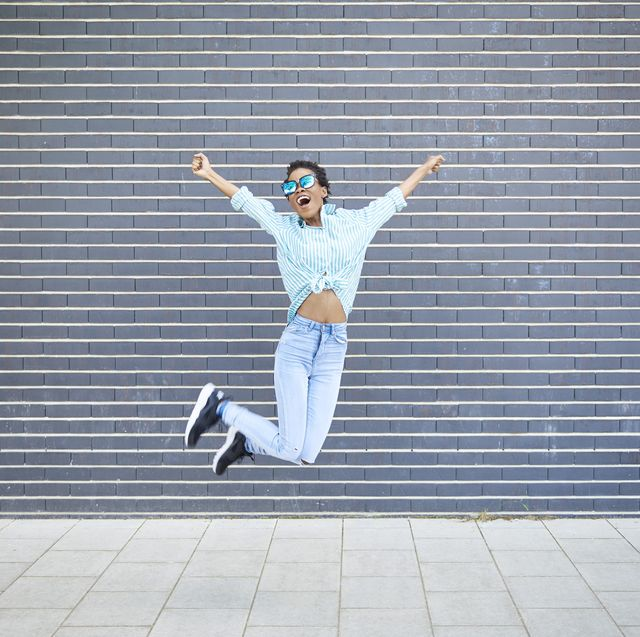 happy woman jumping in the air in front of grey facade