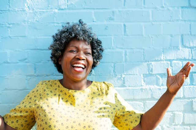 happy woman laughing with arms up
