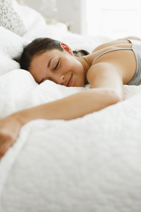 Happy woman laying on bed