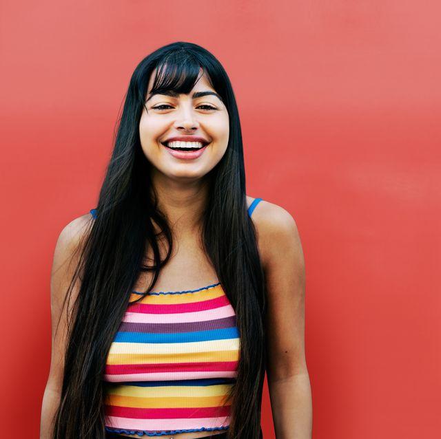 happy woman looking at camera, red wall