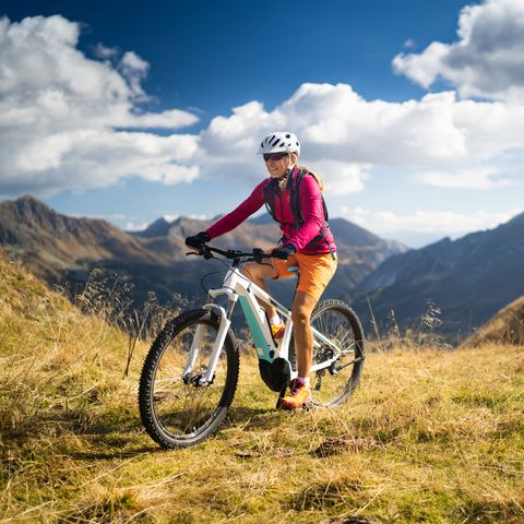 27b6f99fe12 happy woman on electric mountain bike high up in european mountains