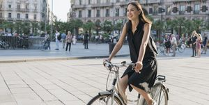 Happy woman riding bicycle standing on city street
