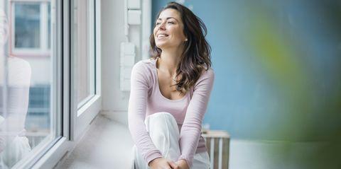 mujer feliz y sana mirando por una ventana