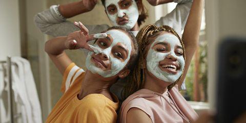 Happy woman taking selfie with friends wearing cream