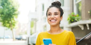 Happy woman with smart phone on street.
