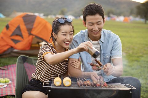 happy young chinese couple barbecuing outdoors