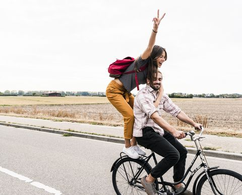 happy young couple riding together on one bicycle on country road