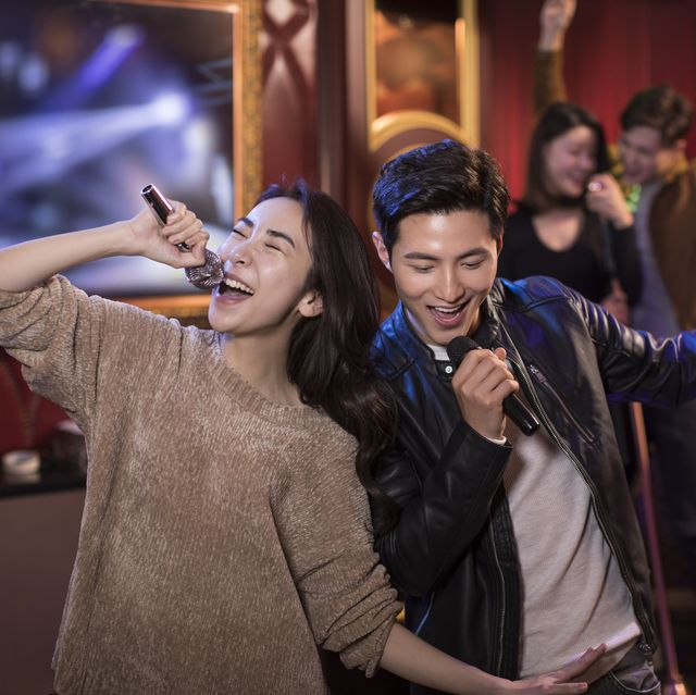 happy young couple singing karaoke in nightclub