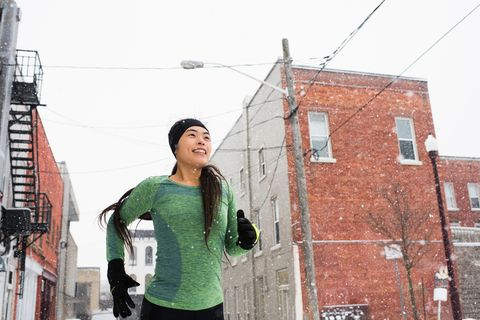 Happy young female runner in knit hat running in snowy street