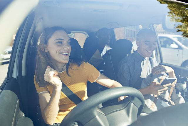 happy young woman dancing with friends in car