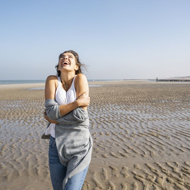 happy young woman hugging self while standing at beach against clear sky