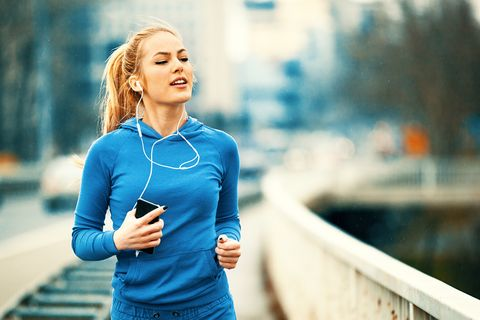 Happy Young Woman Listening Music While Jogging On Bridge