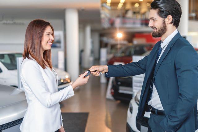 happy young woman receiving car keys for car salesman