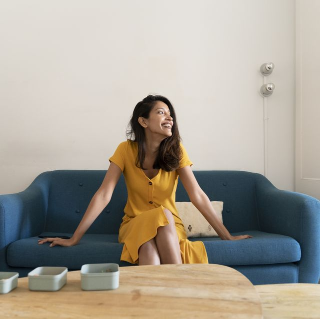 happy young woman sitting on couch looking sideways