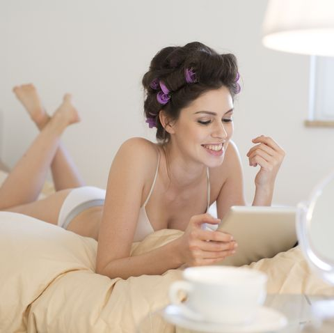 happy young woman with curlers lying in bed using tablet