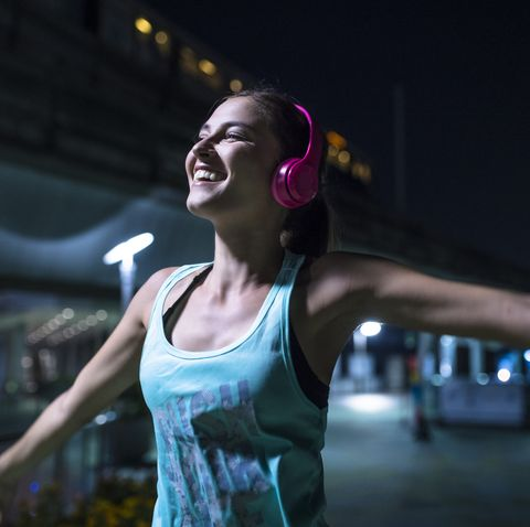 happy young woman with pink headphones listening to music in modern urban setting at night
