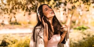Happy Young Women is Listening to the Music in Park