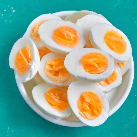Sliced hard boiled eggs on color background  Nutrition concept
