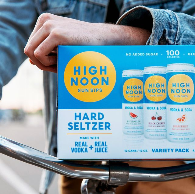 man on bike holding variety pack of high noon hard seltzer