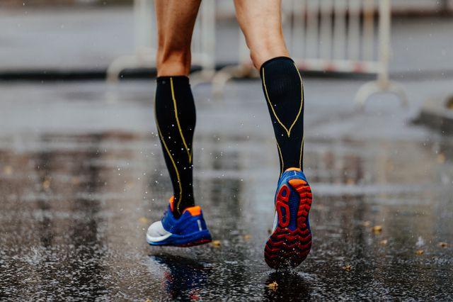 feet male runner in compression socks running on wet asphalt