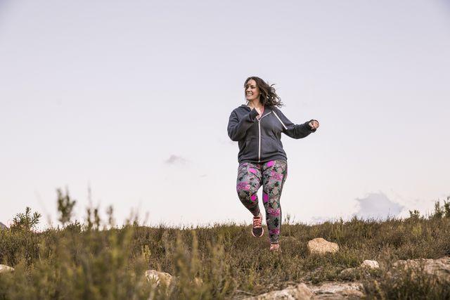 vrouw aan het hardlopen op het gras en is blij