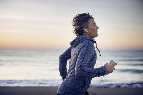vrouw hardlopen over strand met telefoon in hand