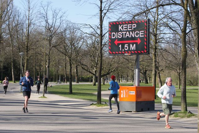 people running  pass a sign urging people to practice social distancing and keep 15 meters at the vondelpark on march 22, 2020 in amsterdam,netherlandsthe dutch government ordered all dutch schools, cafes, restaurants, coffeeshops, sex clubs and sport and fitness clubs to be closed as the government sought to prevent the further spread of coronavirus in the netherlands  photo by paulo amorimnurphoto via getty images