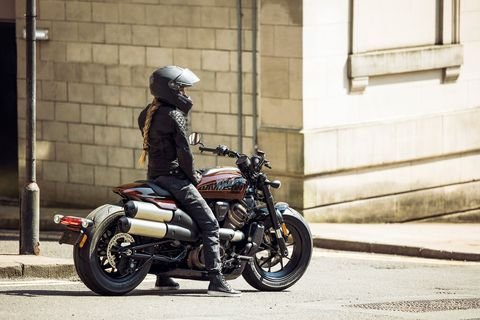 Woman sitting on Harley Davidson Sportster s motorcycle