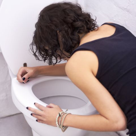 woman hunched over toilet vomiting