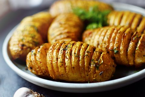 hasselback potatoes baked accordion potatoes delicious vegetables food in a gray clay plate, close up