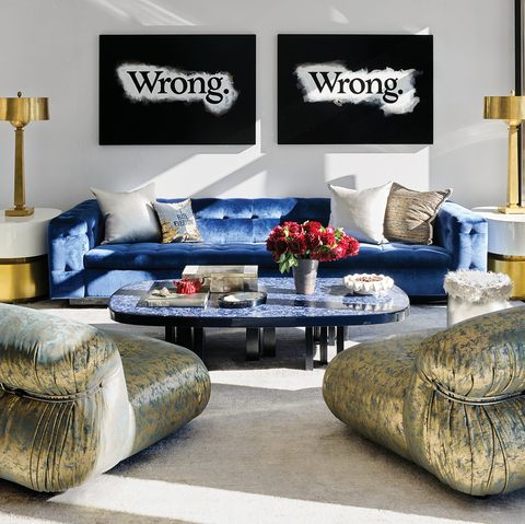 Living room with large blue tufted sofa and pop art