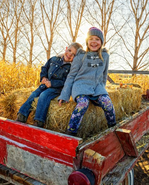 a brother and sister preparing to go on a hay ride
