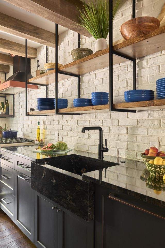 ferrarini and co's philadelphia gallery kitchen with open shelving, black counters and cabinets and white faux brick walls