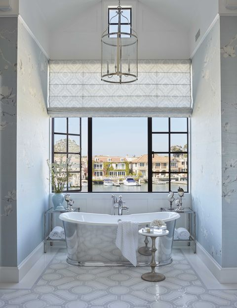 main bathroom, with silver bath tub overlooking views of water, blue wallpaper
