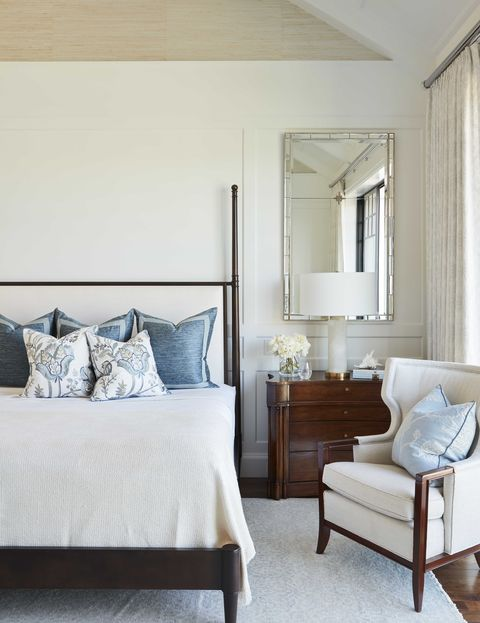 main bedroom, white area rug with white sitting chair, wooden bed frame with bed and white linen