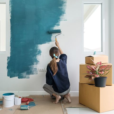 woman painting a wall blue